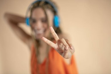 Smiling young African American female in blue headphones, listening to music, showing peace sign