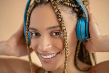 Smiling young African American female touching blue headphones, listening to music