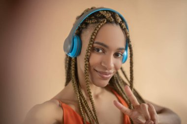 Smiling young African American female in blue headphones, showing peace sign, making selfie