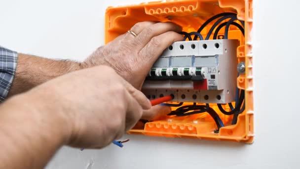 Video o rukou elektrikáře, který vkládá a blokuje kabel v jistič v elektrickém panelu domovní instalace. Stavebnictví.