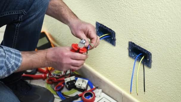 Elektrikář technik pracovník s kabelem cutter kleště snížit elektrický kabel v rezidenční elektrického systému. Stavební průmysl. Budova. Záběry.