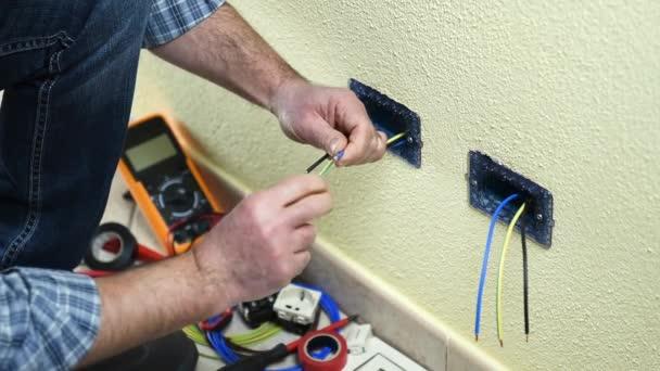 Elektrikář technik pracovník vloží a řeší kabely elektrické zásuvky bytové elektrického systému. Stavební průmysl. Budova. Záběry.