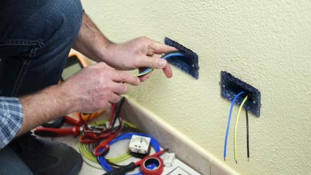Elektrikář technik pracovník vložit elektrické zásuvky do držiteli rezidenční elektrického systému. Stavební průmysl. Budova. Záběry.