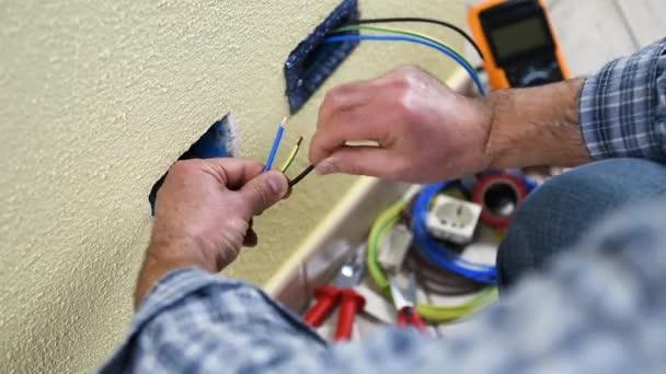 Elektrikář technik pracovník připraví elektrické kabely rezidenční elektrického systému. Stavební průmysl. Budova. Záběry.
