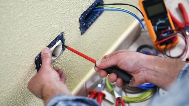 Elektrikář technik pracovník odpojí zásuvky bytové elektrického systému. Stavební průmysl. Budova. Záběry