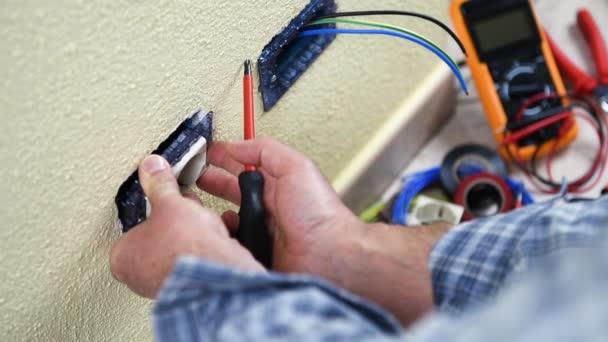 Elektrikář technik pracovník instalovat zásuvky bytové elektrického systému. Stavební průmysl. Budova. Záběry.