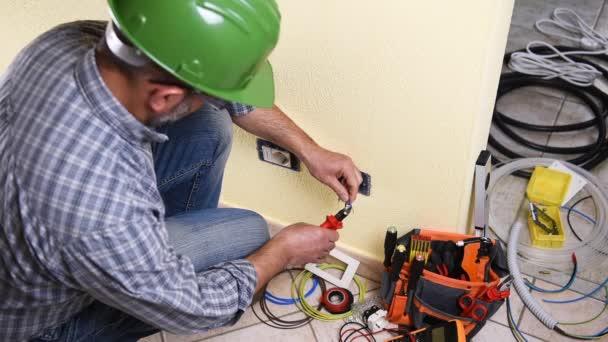 Elektrikář technik pracovník připraví elektrický kabel v rezidenční elektrického systému. Stavební průmysl. Budova. Záběry.