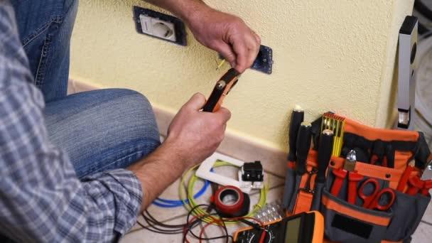 Elektrikář technik pracovník připraví elektrický kabel a s šroubovák přilne k terminálu v rezidenční elektrického systému socket. Stavební průmysl. Budova. Záběry.