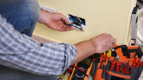 Elektrikář technik pracovník s multimetr měří napětí v elektrické zásuvce v obytné systému. Stavební průmysl. Budova. Záběry.