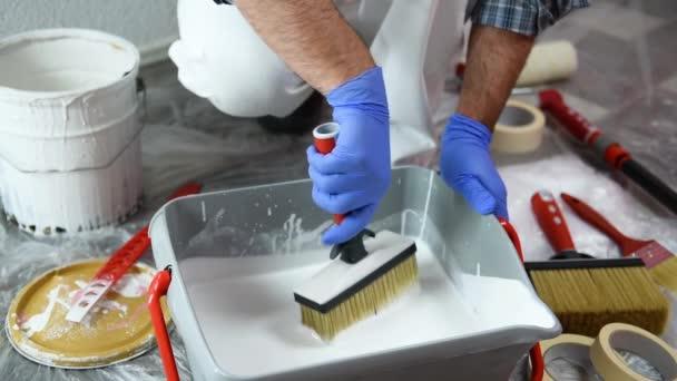 Malíř kavkazského malíře v bílých šneku, ponořte kartáček do nádoby bílou barvou. Stavebnictví. Záběry.