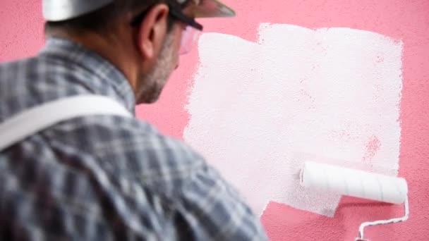 Kaukasischer Maler in weißen Overalls, mit Helm und Schutzbrille. mit der Walze die rosa Wand mit weißer Farbe bemalt. Bauwirtschaft. Bildmaterial.