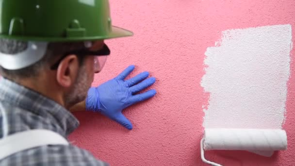 Caucasian house painter worker in white overalls, with helmet and protective goggles. With the roller paints the pink wall with white paint. Construction industry. Footage.