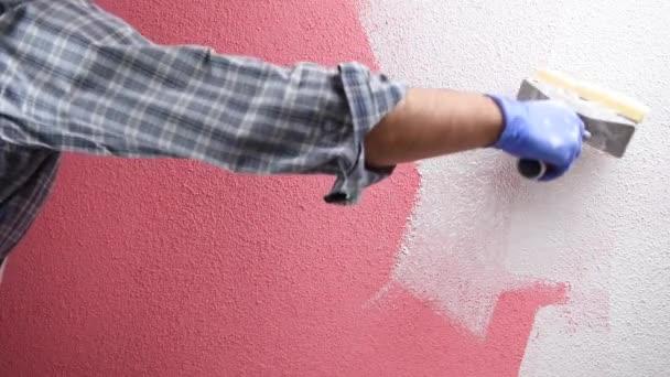 Der kaukasische Maler, Arbeiter in weißen Overalls, streicht die rosa Wand mit der weißen Farbe mit dem Pinsel. Bauwirtschaft. Bildmaterial.