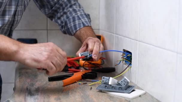Elektrikář technik pracovník s šroubovák, kterým elektrický kabel do zásuvky terminálu v rezidenční elektrického systému. Stavební průmysl. Budova. Záběry.