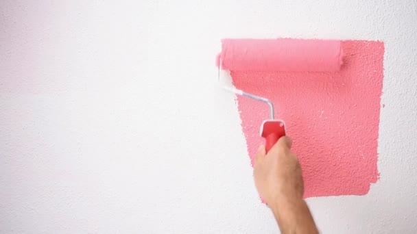 Kaukasischer Hausmaler Arbeiter mit Walze bemalt die Wand mit rosafarbener Farbe. Bauwirtschaft. Bildmaterial.