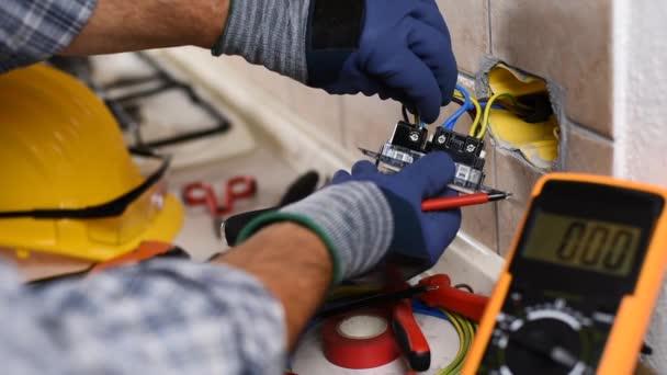 Elektrikář při práci se šroubovákem upevňuje kabel v zásuvkách bytového elektrického systému. Stavební průmysl. Záběry.