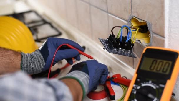 Elektrikář při práci s testovačem měří napětí v zásuvkách bytového elektrického systému. Stavební průmysl. Záběry.