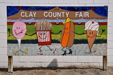 BARNSEVILLE, MN, July 12, 2018: The Clay County Fair occurs in Barnesville, Minnesota each year in early July where thousands attend the midway and agricultural displays as displayed in the descriptive art sign.