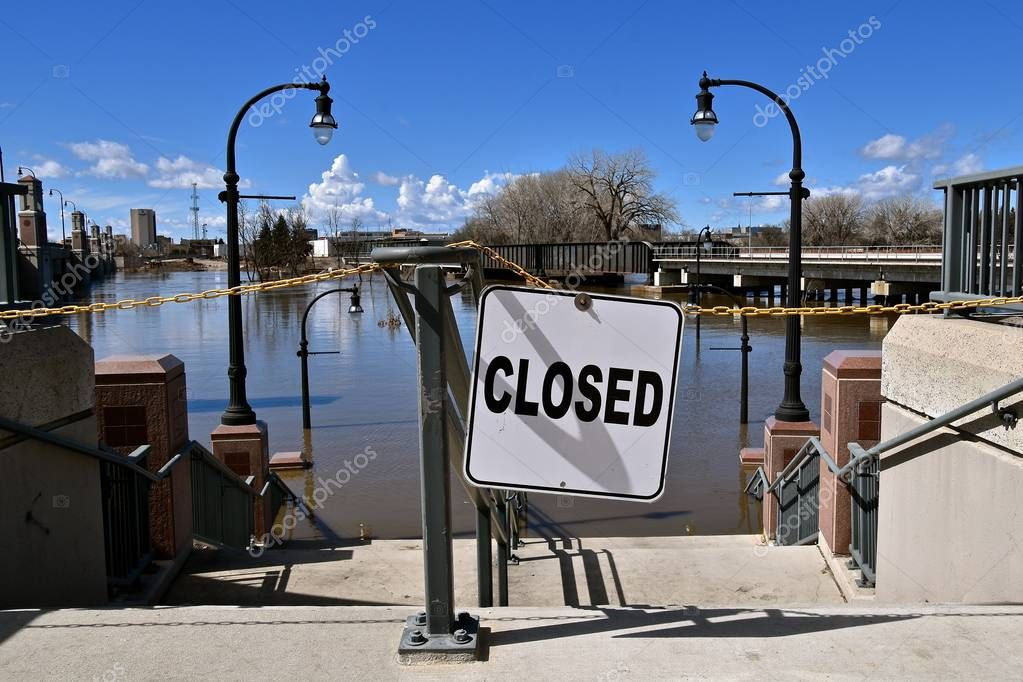 Steps leading to a park and recreation area along a river are closed due to flooding after the spring thaw of snow.