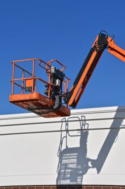 A n empty mechanical hydraulic lift and bucket throws it's shadow abasing the top of a building.