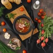 Fotografie Složení potravin krevety polévka s rajčaty a avokádem v černém misku na dřevěné desce s zeleninou a nádobí