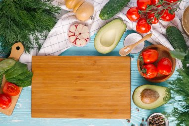 Ingredients for cream of avocado soup around wooden chopping board on blue wooden background