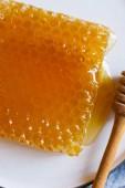 Fotografie Zavřít pohled z čerstvých voštiny na desce se naběračka medu