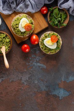 Crispy rice cakes with avocado puree, eggs and tomatoes