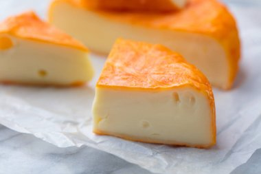 Cheese with washed orange rind. French or German. Marble table background.