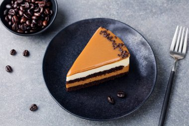 Caramel cake, mousse dessert on a plate. Grey stone background. Top view.