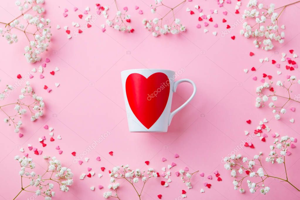 Romantic cup with white flowers and sugar colorful hearts. Pink pastel background. Top view. Copy space.