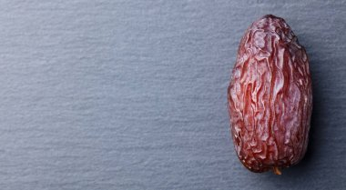 Fresh Medjool Dates. Slate stone background. Top view. Copy space.