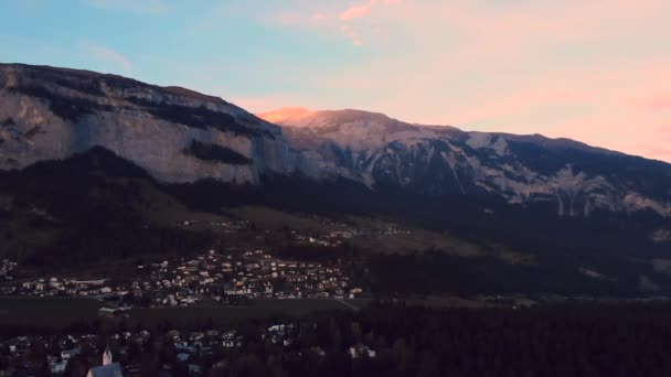 Aerial fly above the forest on Switzerland Alps at sunset - sunrise with lights at mountain top, 4K