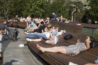 People sunbathe on a park bench