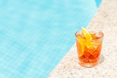 Negroni cocktail  near a pool at the resort bar or suite patio. Luxury resort, vacation, room service concept. Horizontal