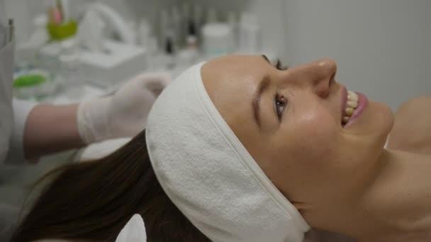 Usmívající se žena leží na gauči kosmetika, kosmetička začíná tvář jedno ošetření