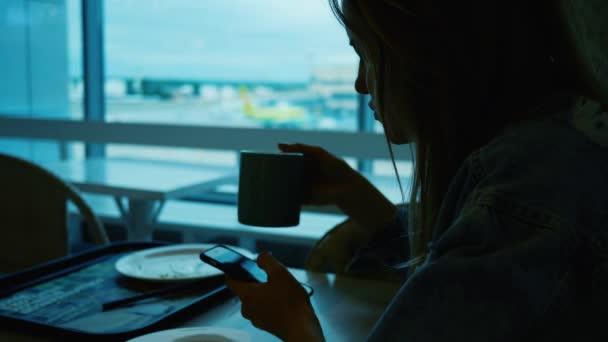 Frau trinkt Kaffee im Flughafen-Café und scrollt auf ihrem Touchscreen-Handy