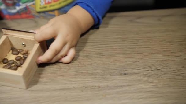 Dítě nastaví dřevěná krabička s fazolemi v mlýnek na kávu ruční. Detailní záběr rukou