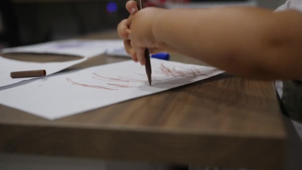 Little hands of baby drawing brown dots with a marker  Boy pokes the paper