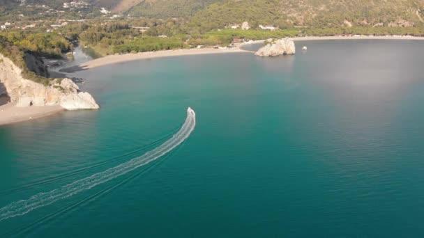 Motoros hajó úszik folyó torkolatánál fás part felé. Légi felvétel a tenger partján. Campania, Olaszország