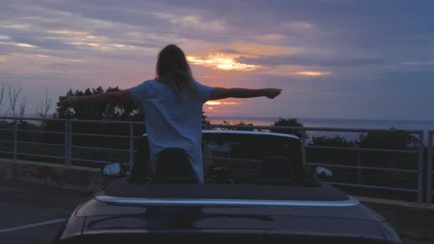 Bezstarostné žena tance v kabrioletem proti západu slunce oblohou