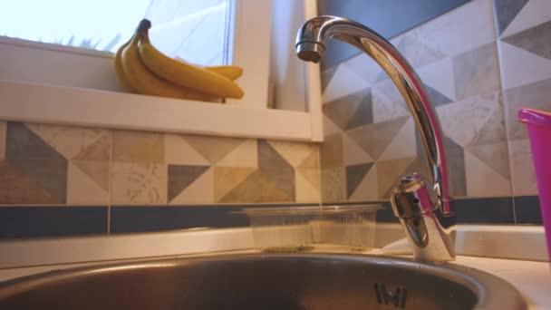 Vodní kapky kape z kohoutku a spadá do kuchyňského dřezu