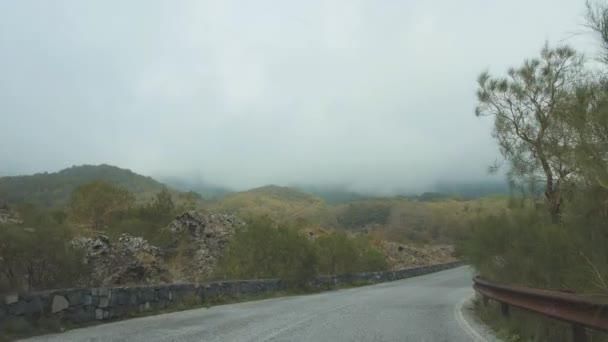 Jízdy po klikaté silnici mezi hory pokryté mraky. Akční snímek