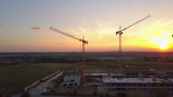 Letecký snímek staveniště s stavební jeřáby proti západu slunce na obloze