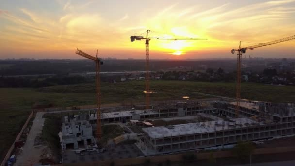 Aerial shot of building site with cranes against sunset sky. Drone moves upwards