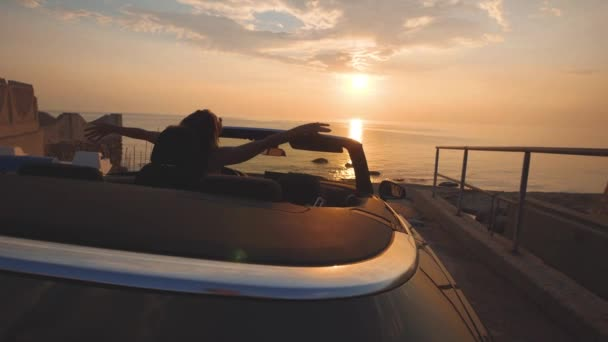 Girl dances on driver place in cabriolet car. Gentle colors of sunset over sea