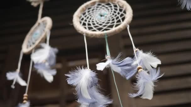 Dreamcatcher con perle e piume bianche. Primo piano del talismano appeso. Basso angolo di ripresa