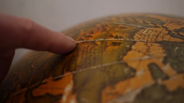 Old vintage globe. Male finger points the worn sphere map. Closeup shot