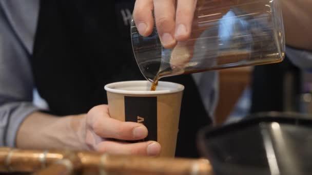 Barista önti kávét üvegből eldobható papír poharat. Férfi kezek közelről