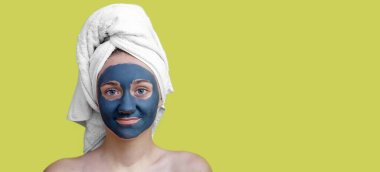 A young teenage girl in a white towel on her head, with a cosmetic clay mask on her face, bare shoulders on a yellow isolated background.The concept of Spa treatments, Facials. Banner, copy space.